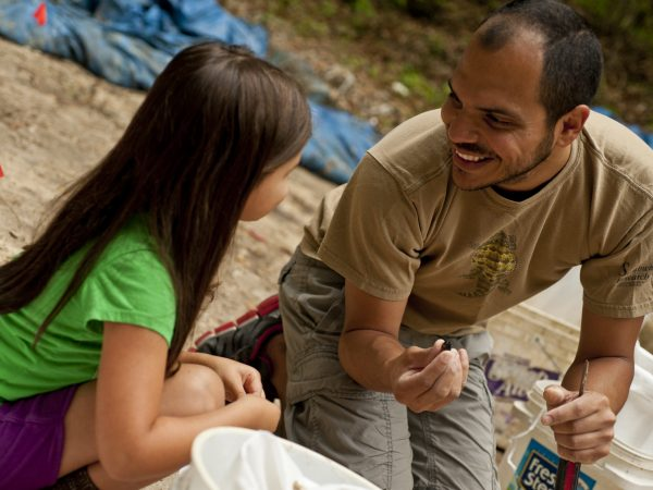 man showing fossil tooth to his young daughter