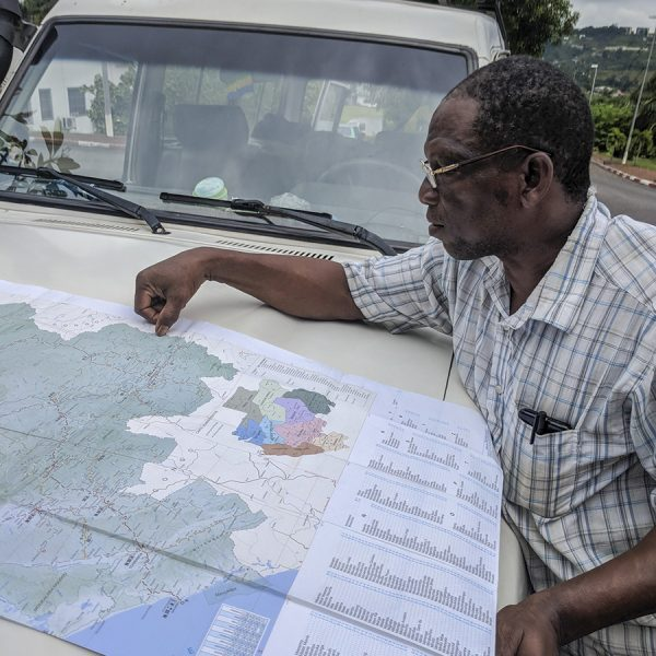 man looking at map on vehicle hood