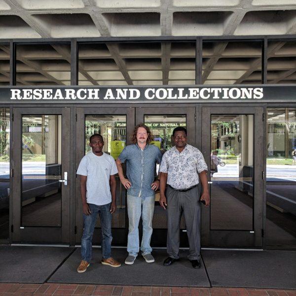 three men in front of museum entrance doors