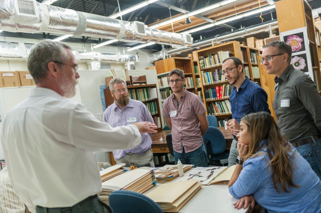 Mark talking to group of people in herbarium