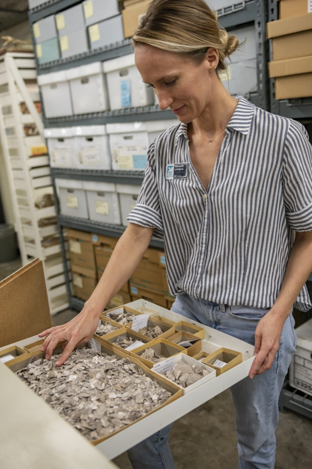 Michelle LeFebvre looks at drawer of shells