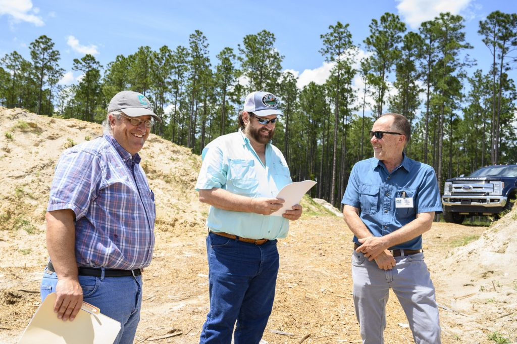 Jonathan Bloch, Eddie Hodge and David Steadman smile overlooking fossil site