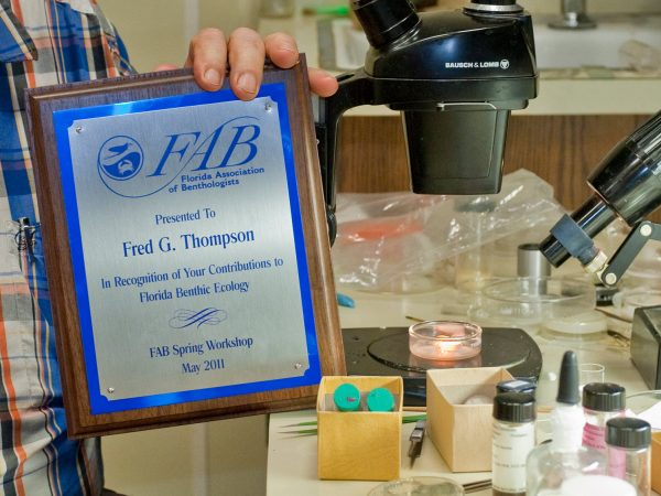 Fred holding award plaque in lab