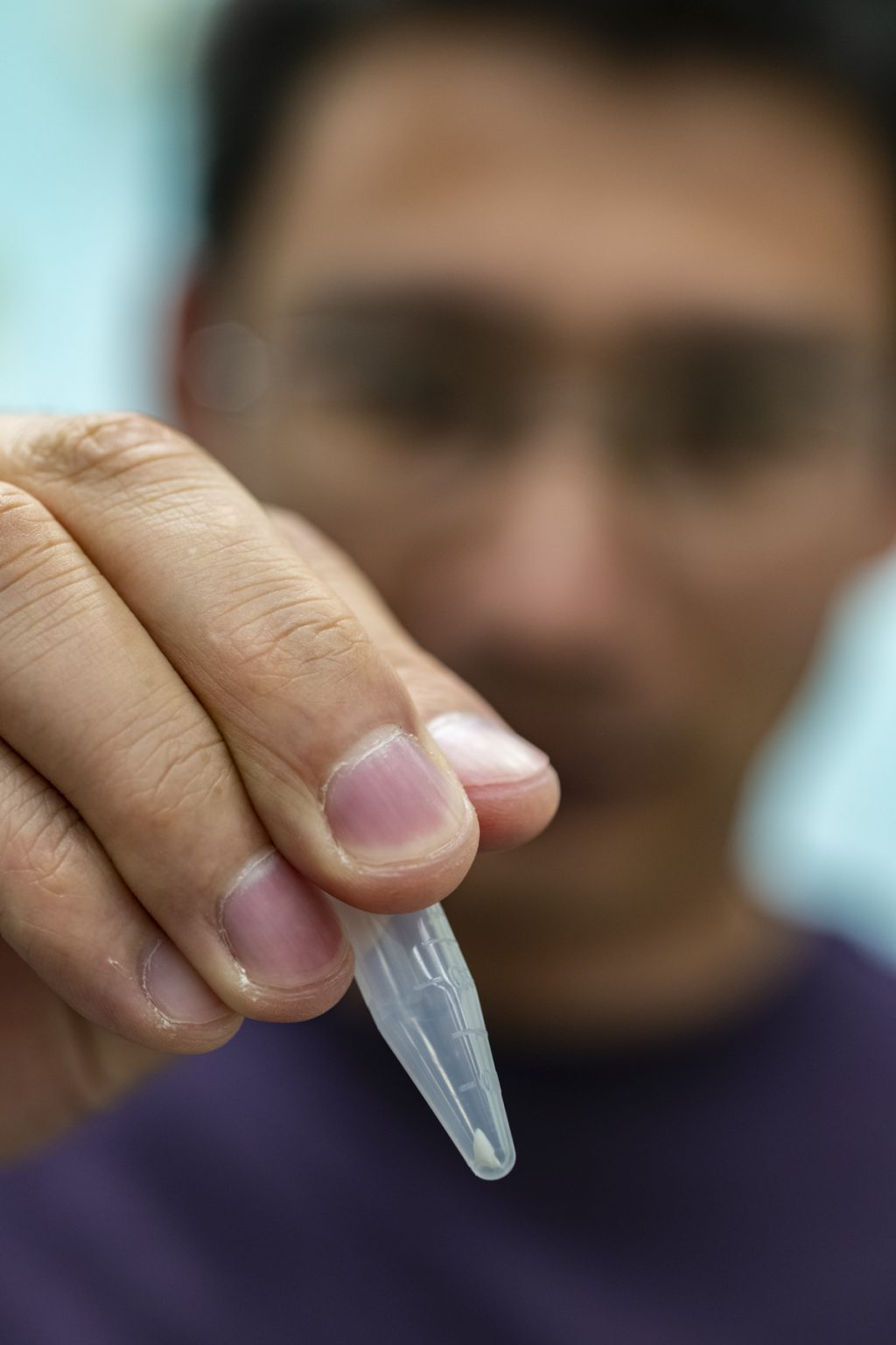 close-up of man holding plastic vial with small tooth fragment