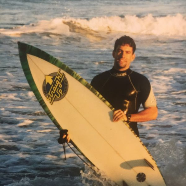 young man in water with surfboard