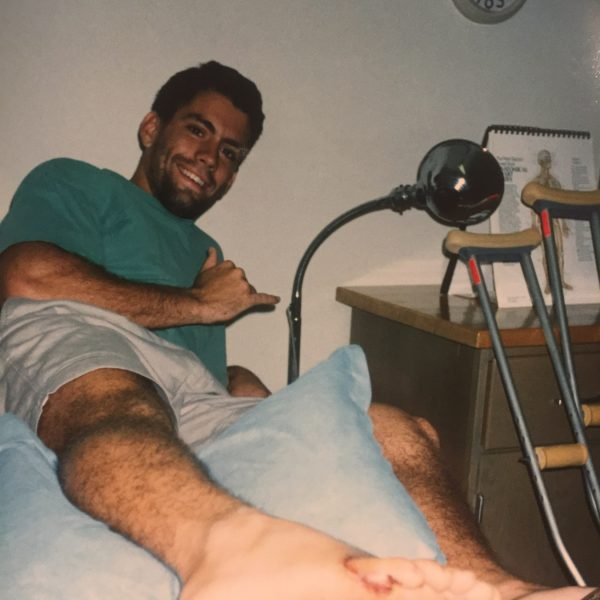 young man smiling with stitched-up foot