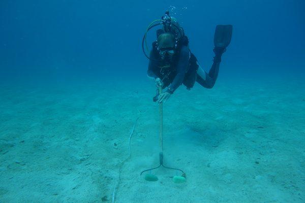 person in scubasuit raking seafloor