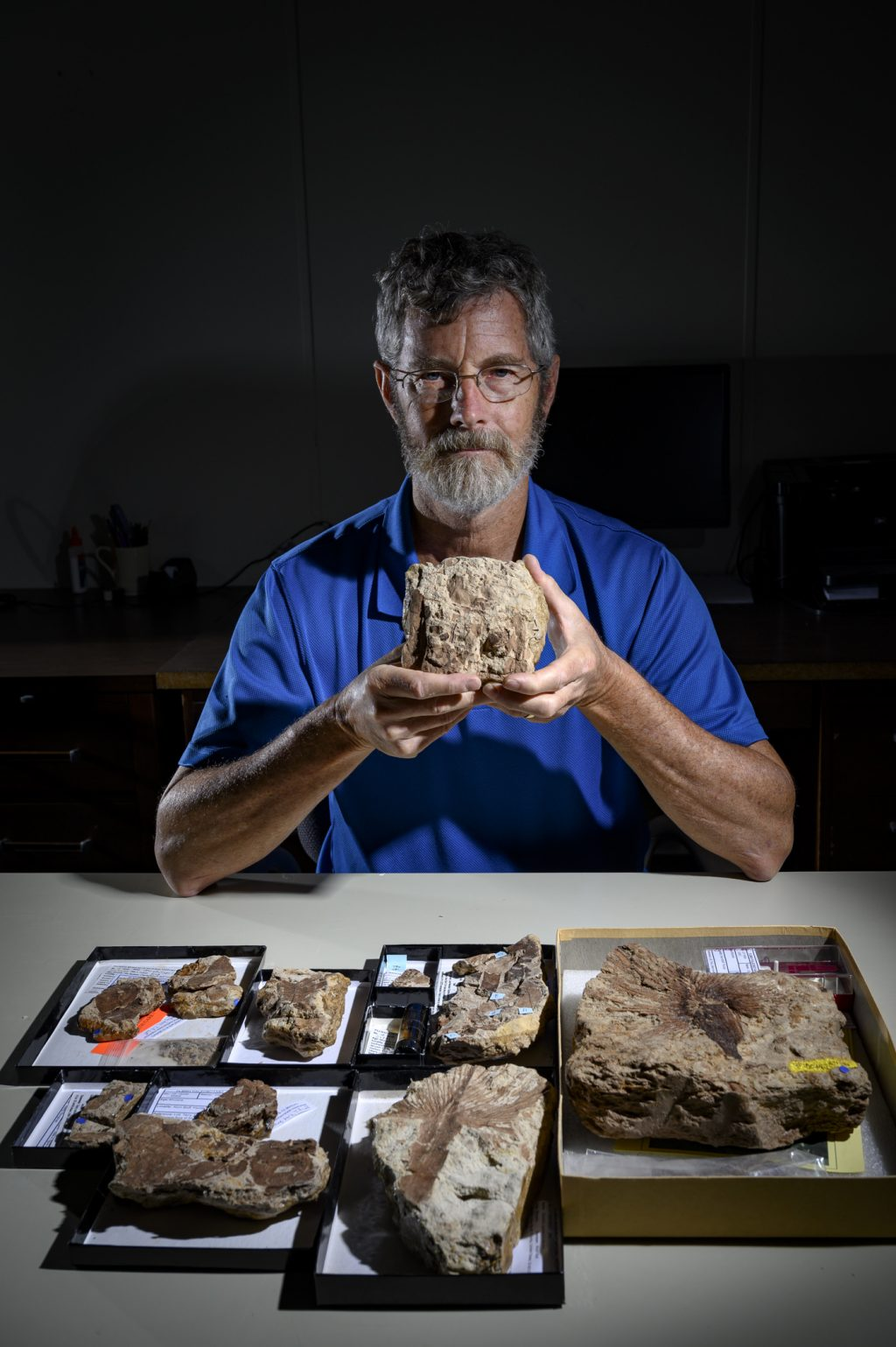 A scientist holding a fossil