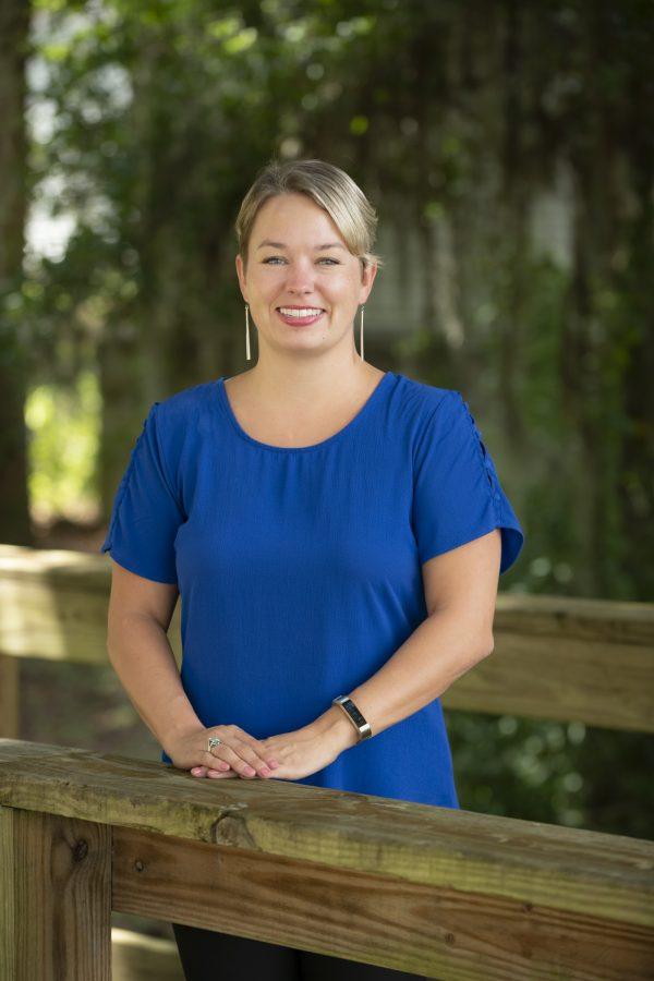 woman in blue dress standing on outdoor boardwalk