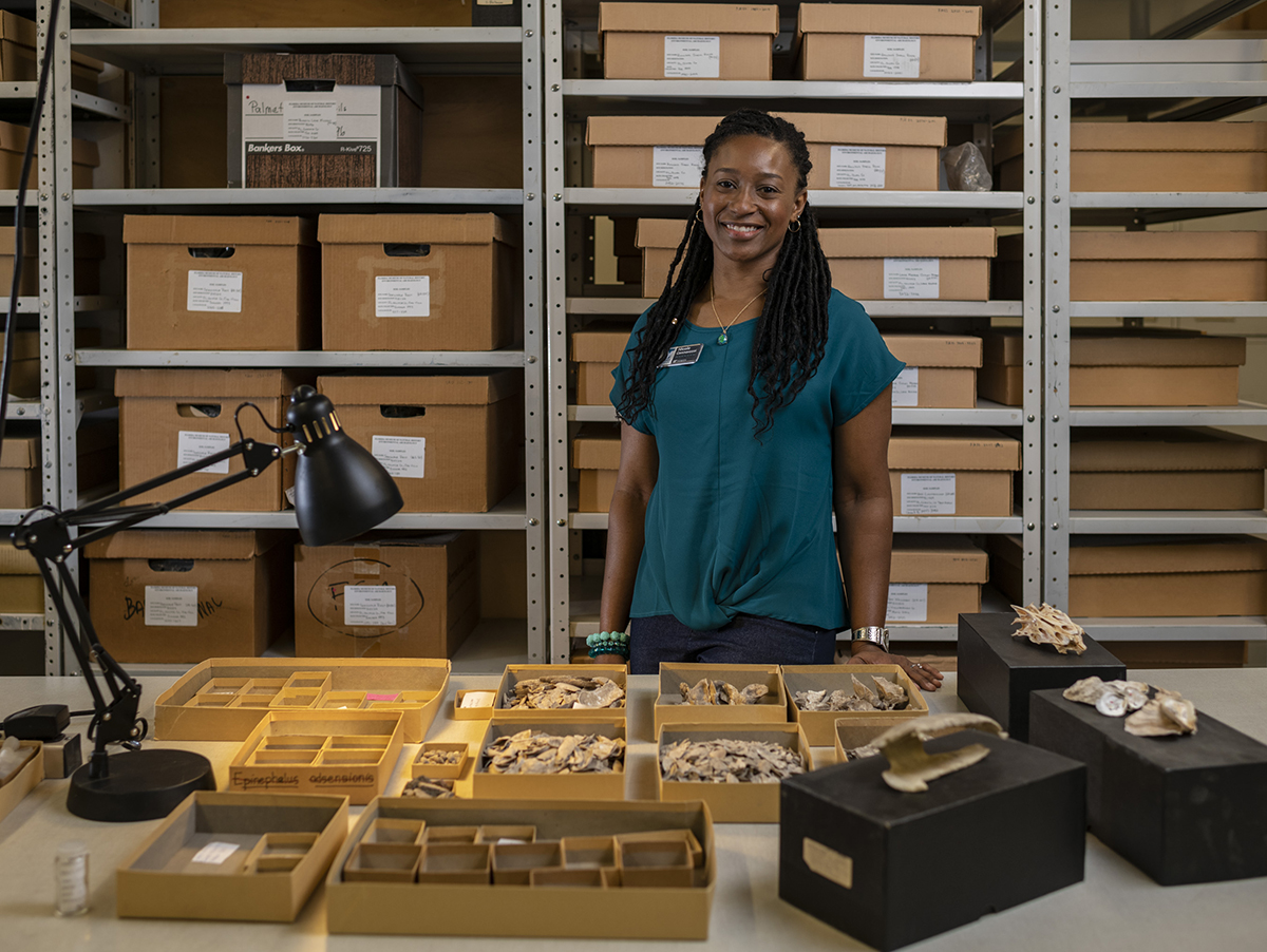 A researcher poses in front of a table of environmental archaeology specimens