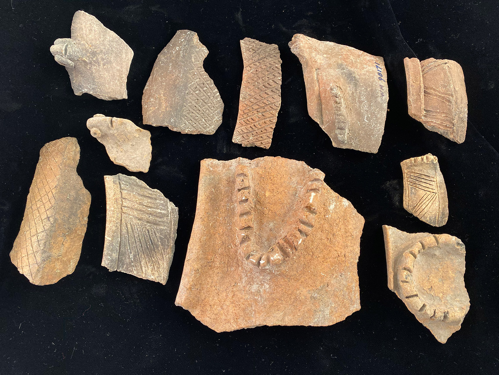 Broken pieces of reddish-orange pottery with different etchings and markings on them sit on a black background