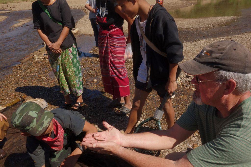 Scientist doing field work with children