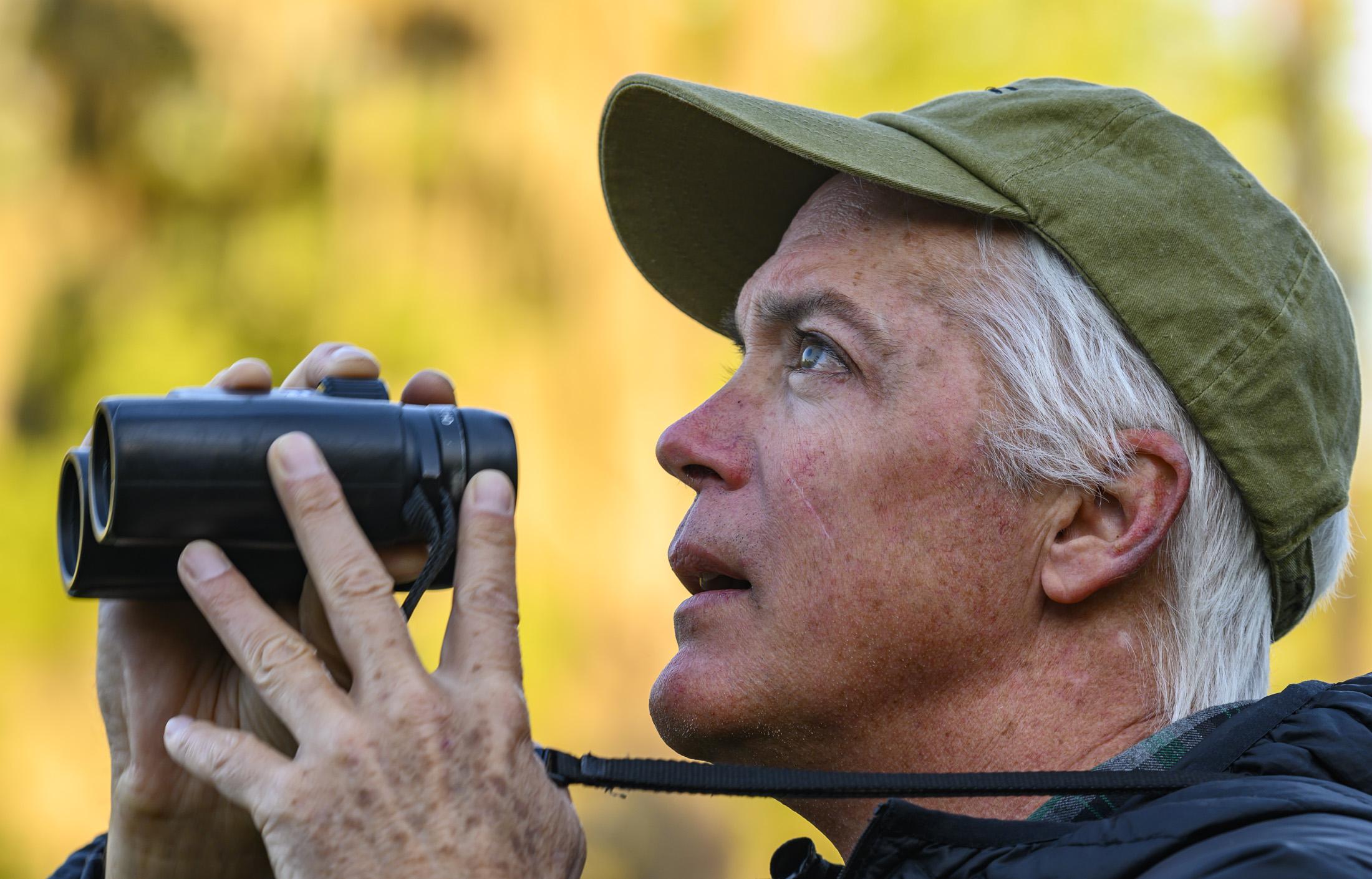 Adam Kent holding binoculars