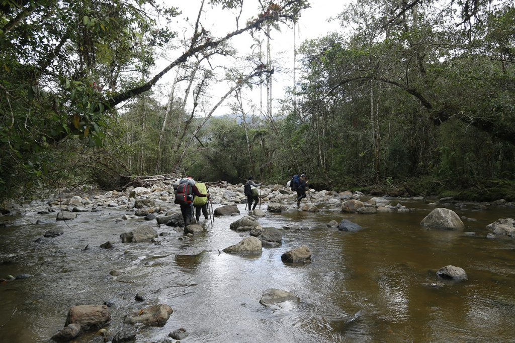 researchers hiking across river