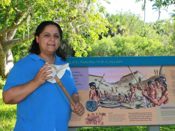 Annisa Karim stands in front of an interpretive sign detailing the Calusa people