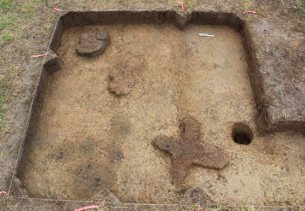 excavation exposing cross-shaped hearth