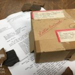 A small cardboard box, typewritten letter, and pottery sherds