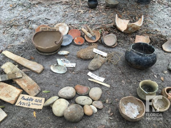 An array of pottery tools with a coil pot in process