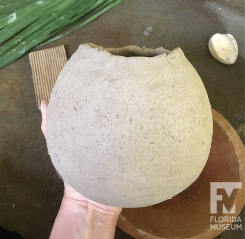 Rounded pot held in hand with rough rim