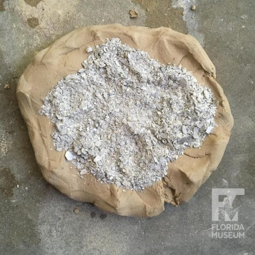 clay with pile of gray crushed shell on top