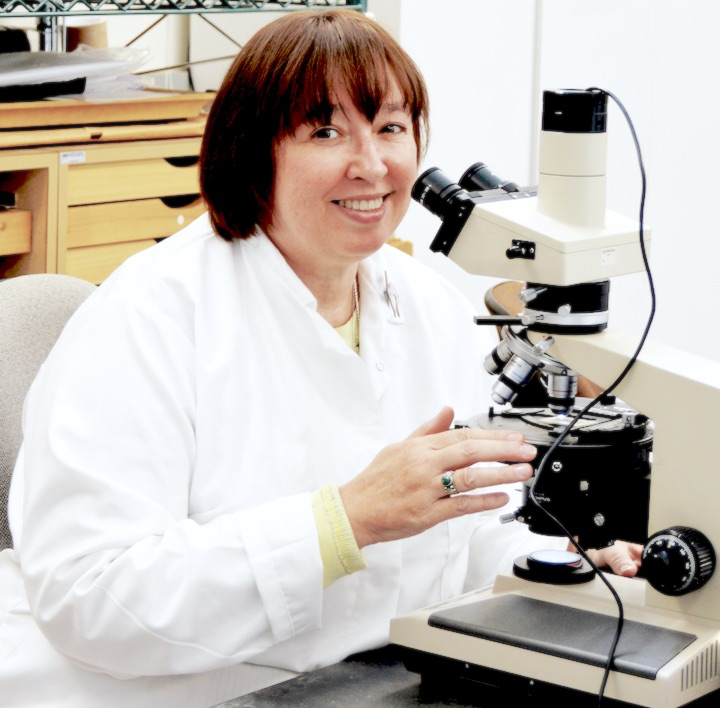 Woman behind a microscope, smiling at the camera