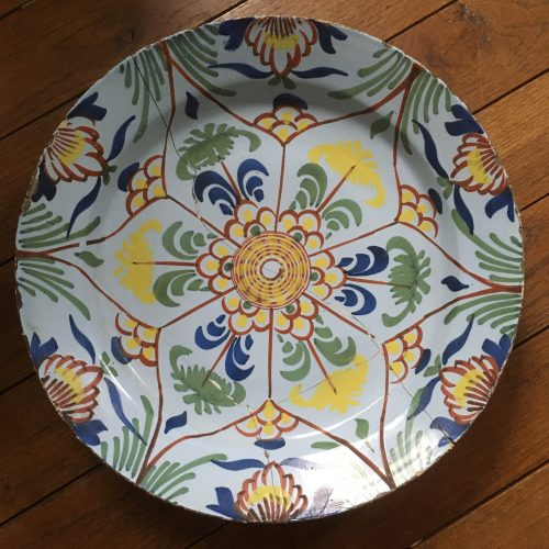 Polychrome tin-enameled earthewnare charger with star/botanical decoration