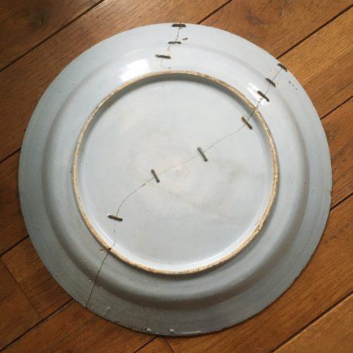 Back side of tin-enameled charger with visible staples