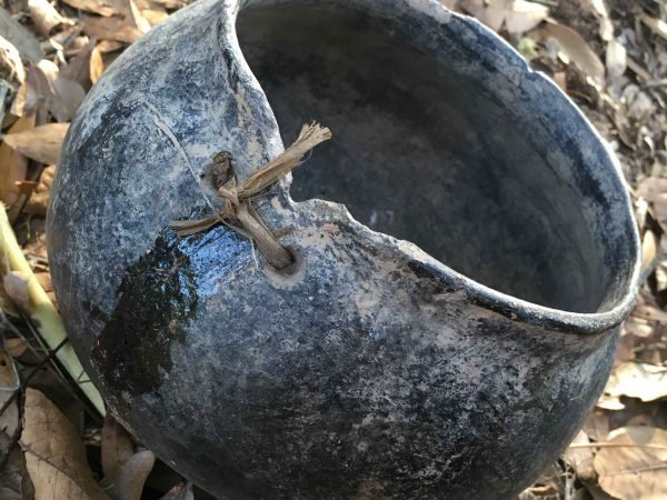 pot sitting on leaves with visible holes lashed with twine closing a crack.