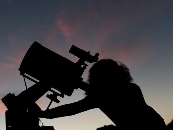 silhouette looking through telescope