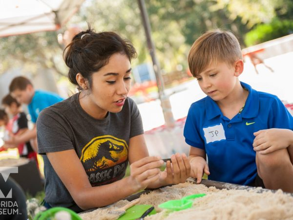 kid learning in fossil dig station