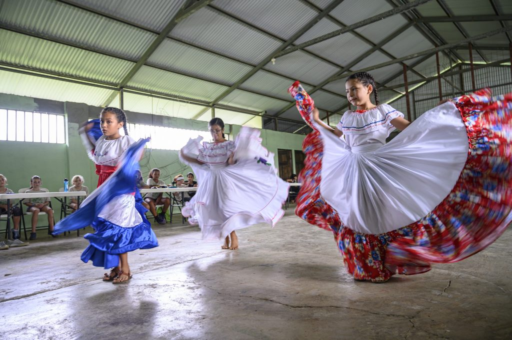 Local children perform traditional dances in colorful dresses in Costa Rica.
