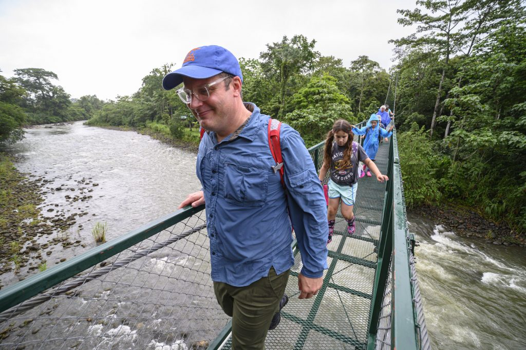 People cross a suspension bridge over a river in Costa Rica.