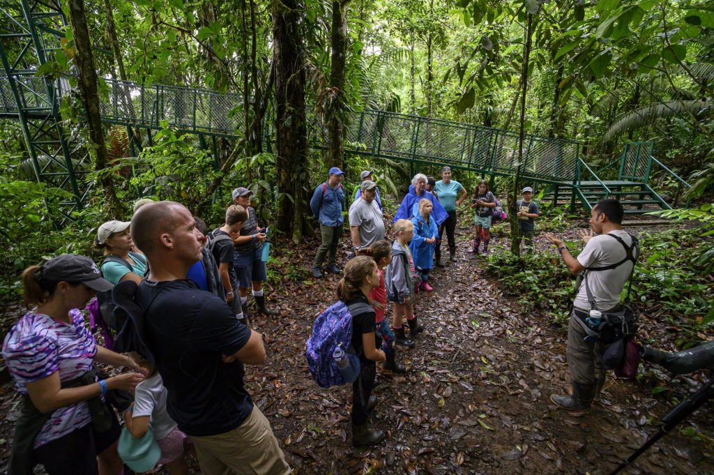 A group listens to a guide at the entrance of a rainforest in Costa Rica.