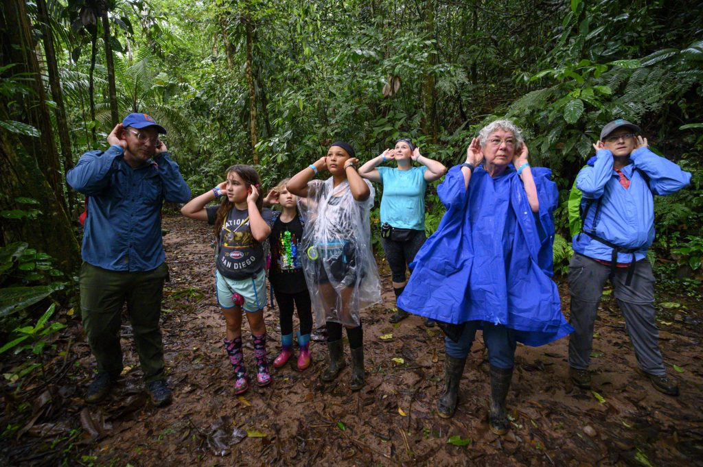 A group of people cup their ears to better hear the calls of howler monkeys in the distance in a rainforest in Costa Rica.