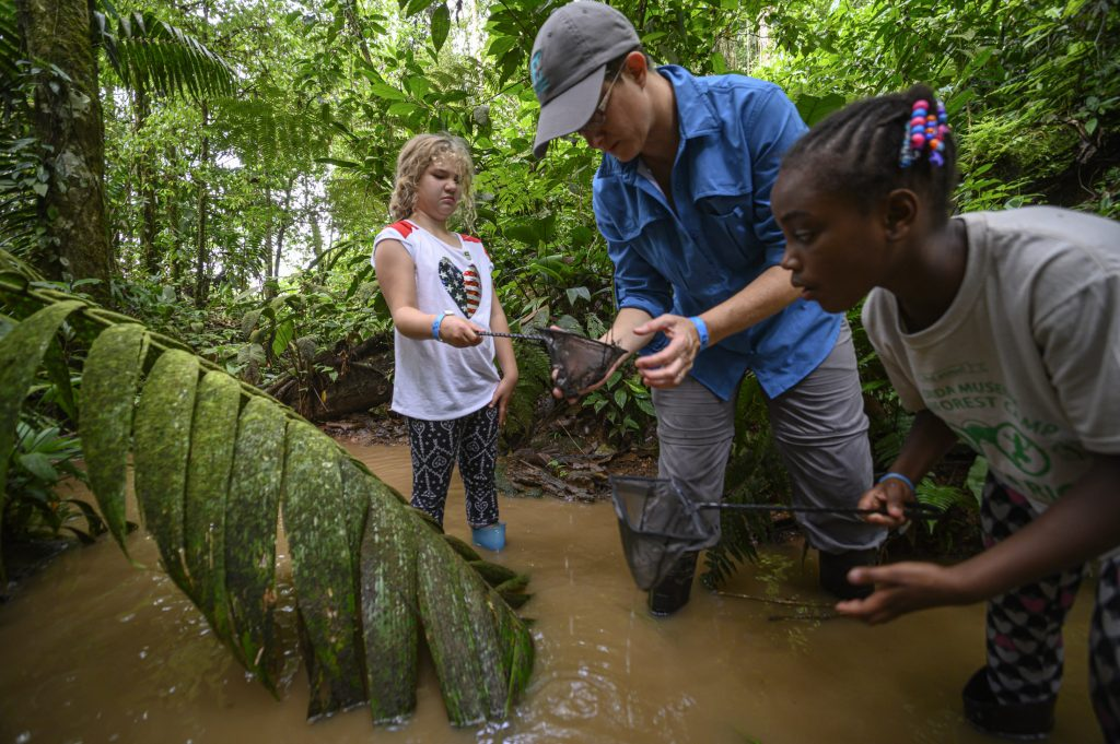 Educator Tina Choe looks in a Childs dip net in a stream in Costa Rica.