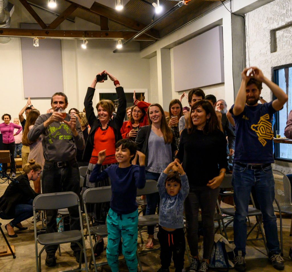 standing audience with some people using their hands to make the shape of shark fins on their heads