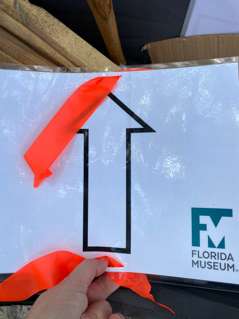 a laminated arrow sign ready to be placed outside for a race