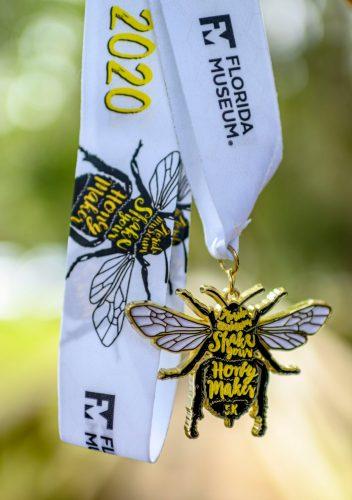 a 5k race medal shaped like a bee