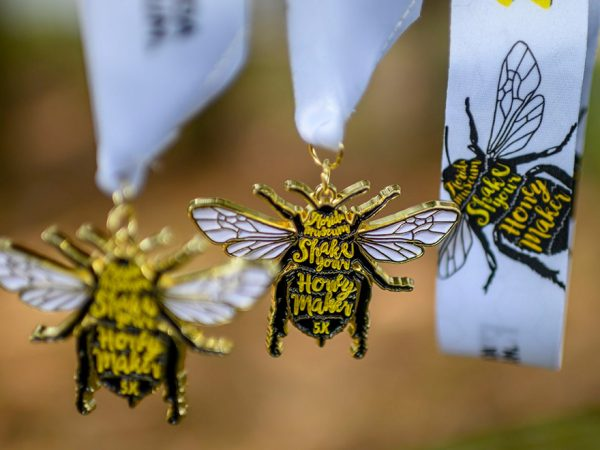 several 5k medals shaped like bees