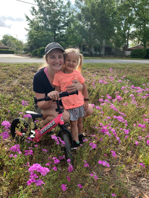 Virtual 5K runners and young girl sanding a patch of pink flowers