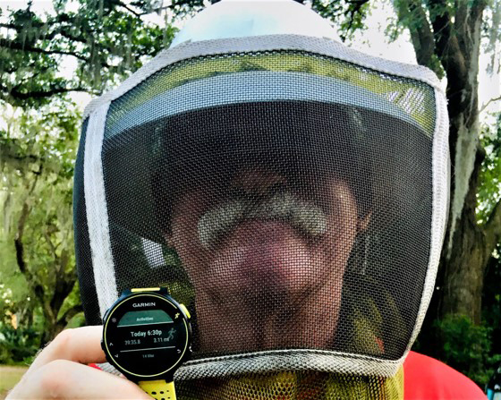 Virtual 5K runner wearing a bee-keepers mask and holding up a smart watch showing the distance he ran.