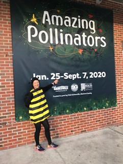 Virtual 5K runner dressed as a bumble bee standing in front of Amazing Pollinators sign.