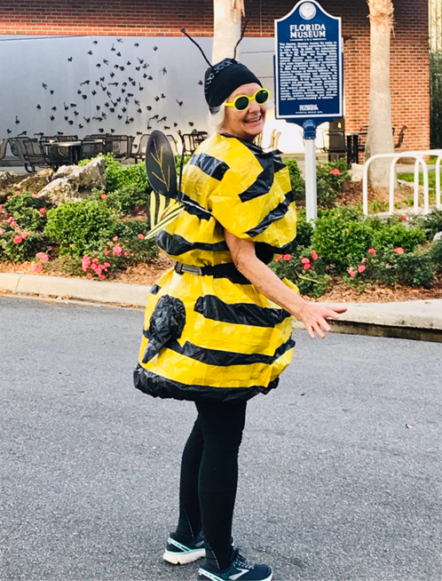 Virtual 5K runner dressed as a bumble bee standing in front of the Florida Natural History Museum.