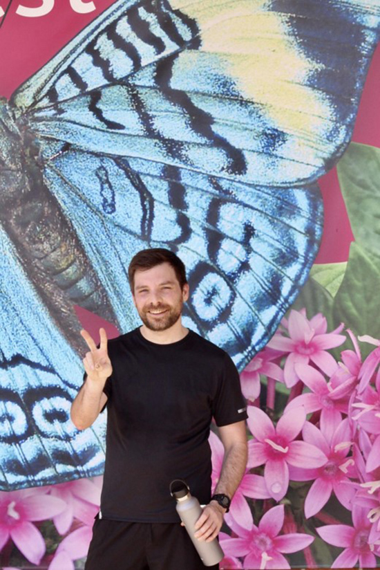 Virtual 5K runner giving the peace sign standing in front of a moth and flower painted mural