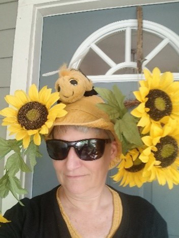 Virtual 5K runner with a hat covered in artificial sunflowers and a large bee-shaped stuff animal