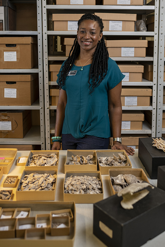 woman stands infront of boxes of oyster shells