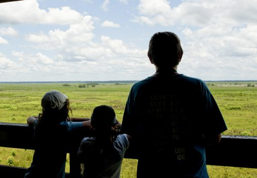several people looking over a sunny prairie