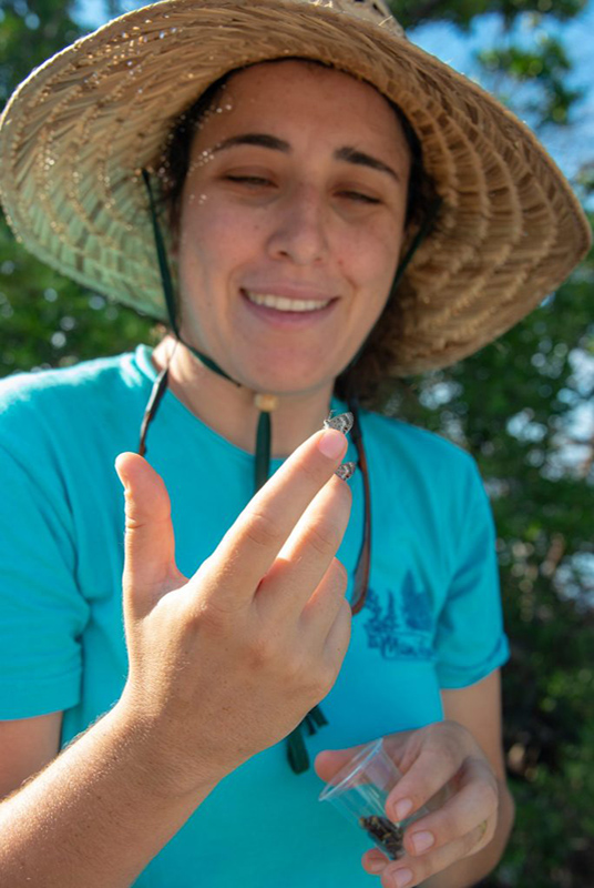 woman in straw hat looking at a small butterfly on the tip of her finger