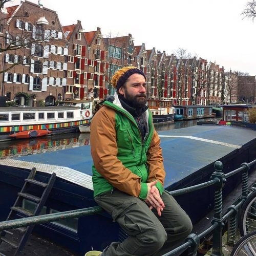 person sitting on rail, canal and river boats in background
