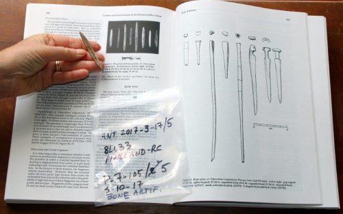 bone artifact shown next to a book